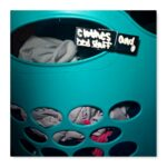 A slate clothes pin on a laundry hamper that says clothes and bed stuff.